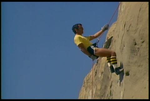 A man rappels down a mountain Live Action