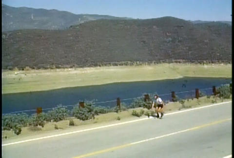 A man rollerblades along a rural highway Stock Video Footage