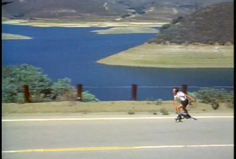 A man rollerblades along a rural highway Footage