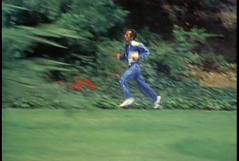 A retro man jogs on a trail through a park Stock Video Footage