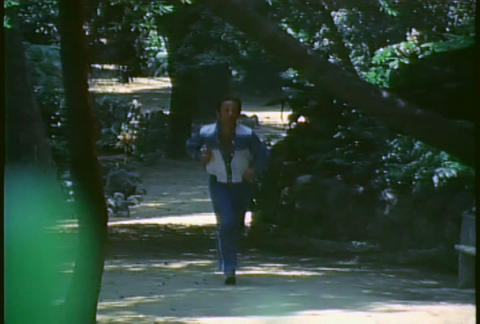 A retro man jogs on a trail through a forest Stock Video Footage