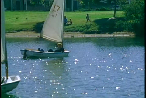 People leisurely float in sailboats on a small lak Stock Video Footage