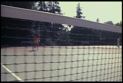 Two people play tennis as seen through the net Footage