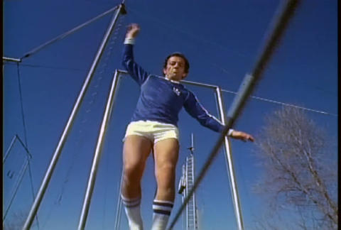A retro man walks on a tightrope in tennis shoes a Stock Video Footage