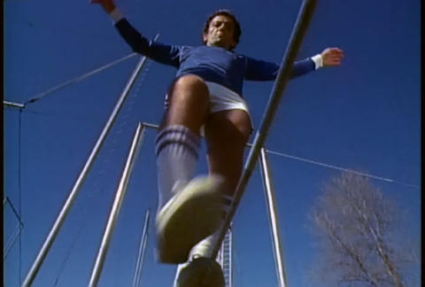 A retro man walks on a tightrope in tennis shoes a Footage