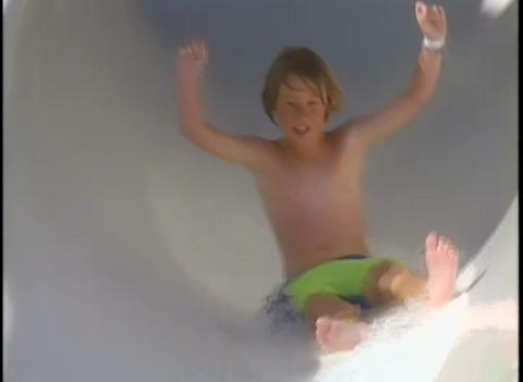 A boy goes backwards down a water slide on an inne Footage