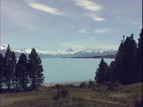 A lake nestles against a mountain range containing Mt. Cook on the South Island of New Zealand Footage