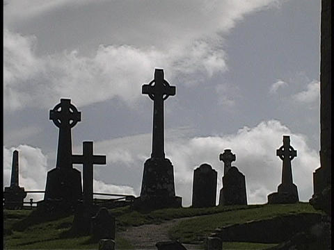 A United Kingdom hillside cemetery's markers stand silhouetted in the golden-hour Footage
