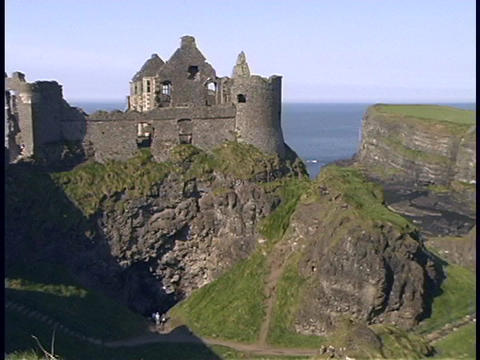 An ancient castle adorns a hill along an Irish coastline Footage