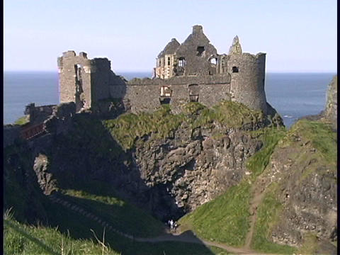 An ancient castle adorns a hill along an Irish coastline Stock Video Footage