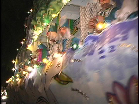 A large duck float glows with lights in a Mardi Gras Parade Footage