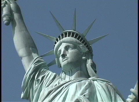 The Statue of Liberty stands with her crowned and solemn face Footage