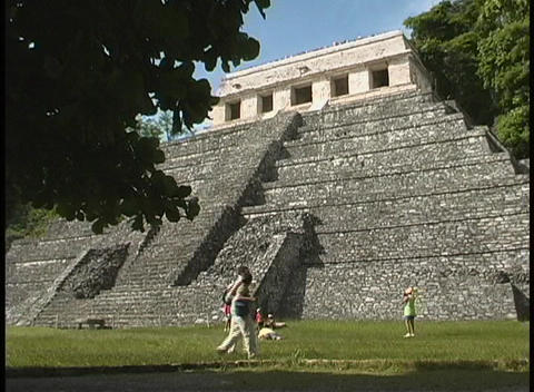 People walk and rest near a large, ancient MesoAmerican stone pyramid Footage