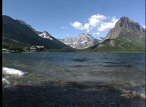 Waves ripple through a glacial lake with strong mountain... Stock Video Footage