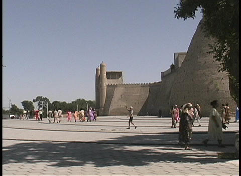 People walk outside The Ark of Emir's Palace in the ancient city of Bukhara, Uzbekistan Footage