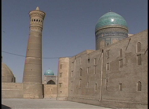 Birds fly around the ancient Kalyan Minaret and two turquoise mosque domes Footage