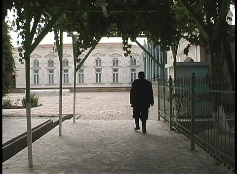 A man walks through a courtyard enclosed by ancient buildings in Bukhara, Uzbekistan Footage