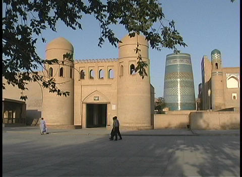 People walk in front of the entrance to the walled city of Khiva, Uzbekistan Live Action