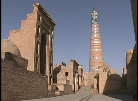 A mosque and minaret adorn the blue sky in Khiva, Uzbekistan Stock Video Footage