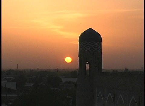 A mosque dome silhouettes the orange sky at golden-hour Stock Video Footage
