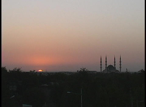 A mosque and minaret silhouette against the pink sky at golden hour Footage