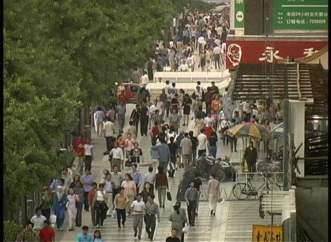 A crowd of pedestrians walk on through downtown Xian, China Stock Video Footage