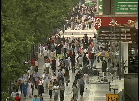 A crowd of pedestrians walk on through downtown Xian, China Live Action