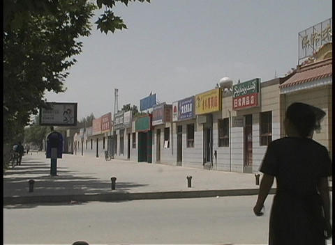A group of people walk by a row of shops in Shache, China Stock Video Footage