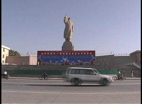 Traffic and bicyclists ride by a large statue of Mao... Stock Video Footage