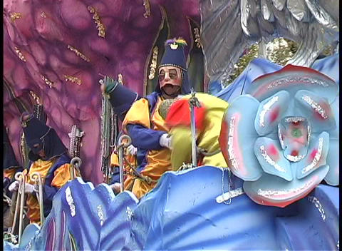 Costumed characters on a Mardi Gras float throw beads to the crowds along the street Footage