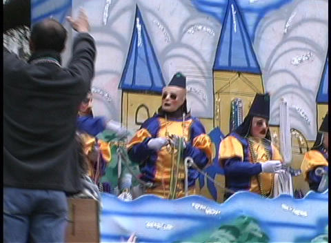 Costumed figures on a float throw out strands of... Stock Video Footage
