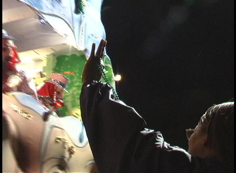A woman catches several souvenirs given out by a passing float during the Mardi Gras parade Footage