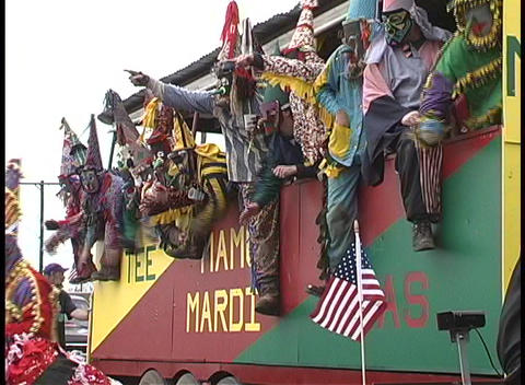 A group of very colorfully costumed men ride together on a Mardi Gras float and wave to the crowds Footage