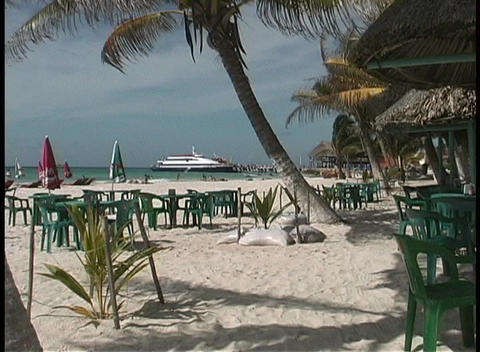 The camera looks past swaying palm trees, outdoor tables and chairs, and beautiful white sand to a c Footage
