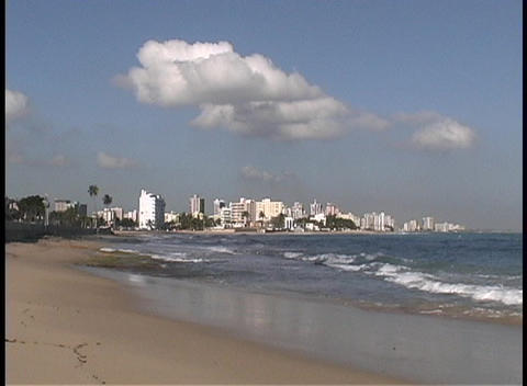Waves break along a sandy beach in front of the San Juan skyline Footage