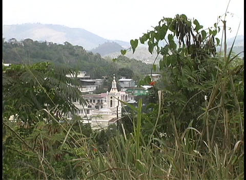 A beautiful white church is seen from a grassy hilltop in Puerto Rico Footage