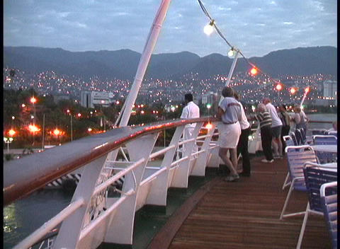Lights adorn the deck of a cruise ship, as passengers... Stock Video Footage