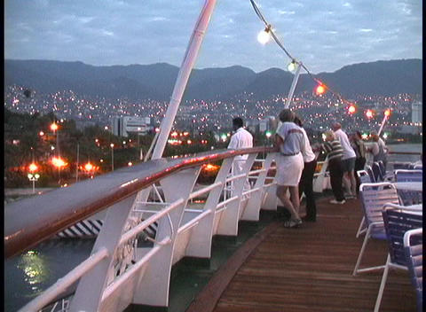 Lights adorn the deck of a cruise ship, as passengers look over the railing at Acapulco at night Footage
