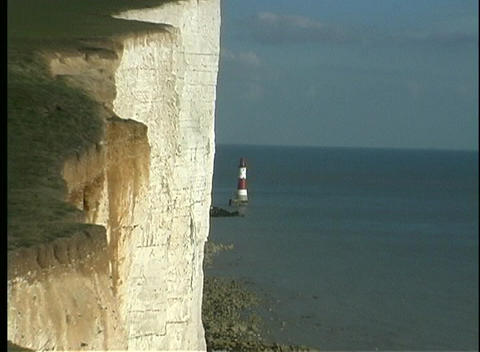 A red and white lighthouse is dwarfed by the majesty of the White Cliffs of Dover Footage