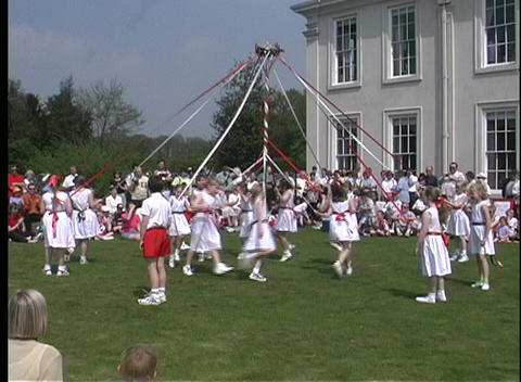 Children dance around a colorful Maypole as they... Stock Video Footage