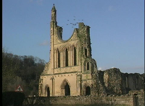 Flocks of birds fly around the remains of a castle or a cathedral seen in Stratford-upon-Avon Footage