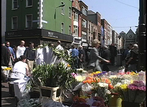 Pedestrians and shoppers pass a flower stand on the corner of a busy street in Dublin Footage