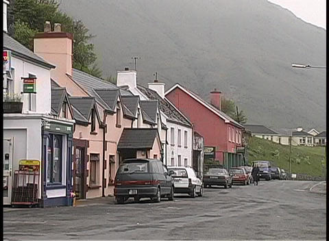 Woman in raincoat strolls through the mist in a small Irish village Footage