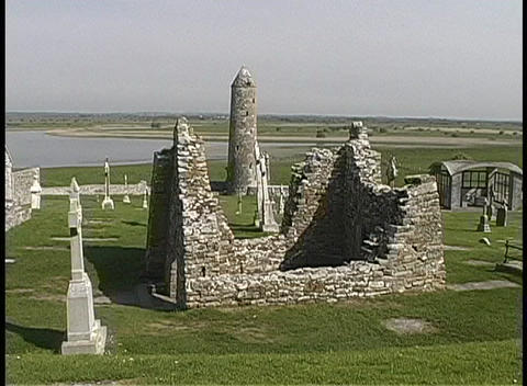 The Round Tower of Clonmacnoise towers above the ruins of Temple Ciaran in Ireland Footage