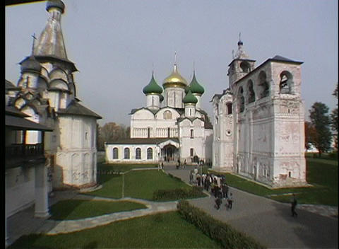 People walk down a grass lined sidewalk to enter the Novgorod Christian Russian Orthodox Church Footage