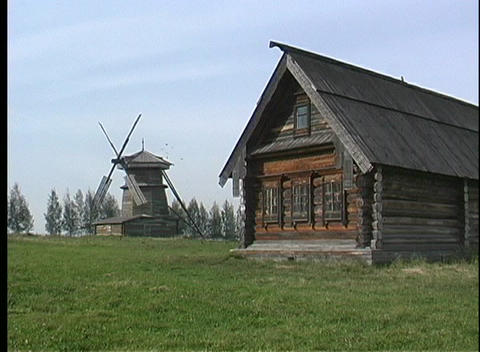 A pan shot of a wooden house and wooden windmill in Russia Footage
