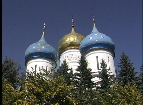 Evergreen trees wave in the breeze as a worms-eye view of domed spires, part of the Sergiev Posad Ru Footage