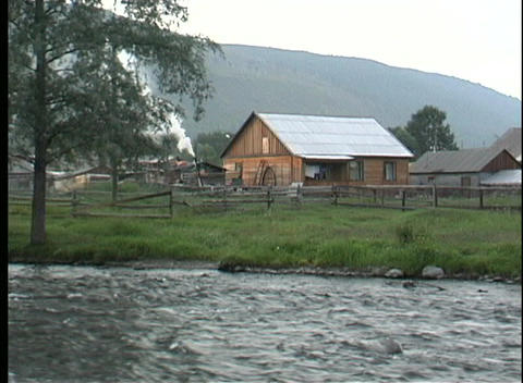 A river flows in front of a rural farmhouse in Kamchatka Peninsula Footage
