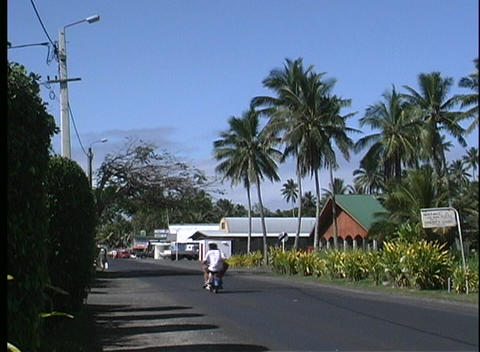 Cars and bikes driving on a city street on Rarotanga one of the Cook Islands in the South Pacific Footage