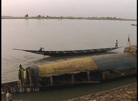 The camera pans across a long boat docked along the shoreline of the Niger River Footage
